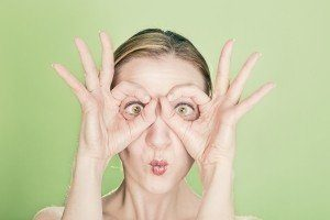 woman with a funny facial expressionlooking between her fingers