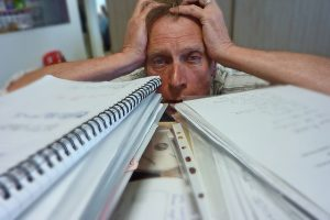 man looking defeated under a mountain of paper