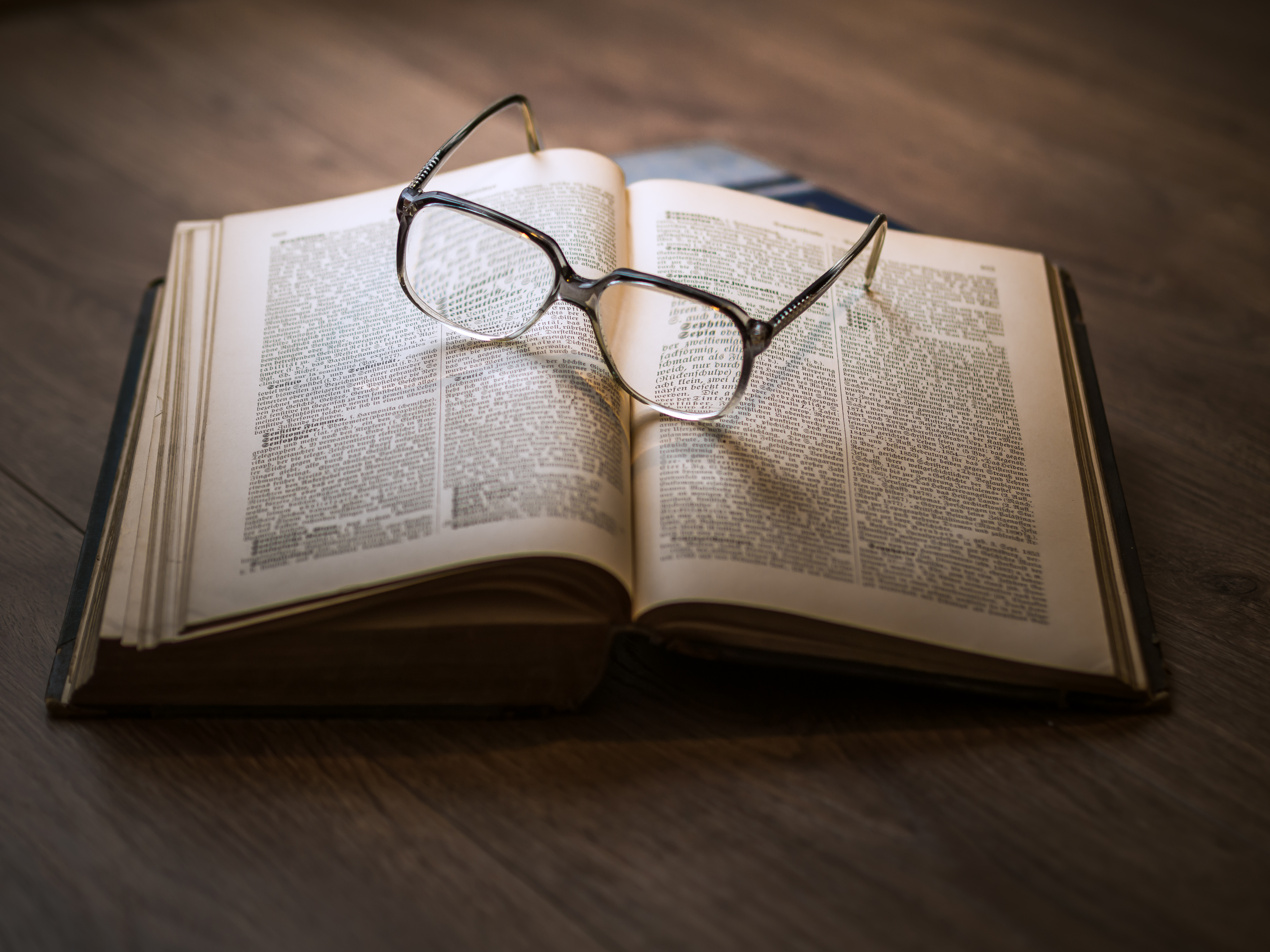 Open book with eyeglasses resting on it