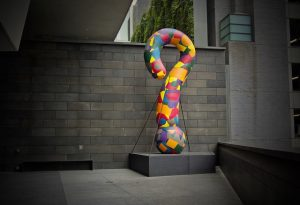 Colorful statue of a question mark on a gray background